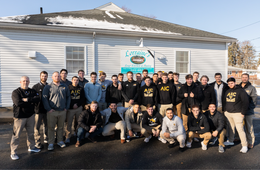 AIC men's baseball team pose outside of Lorraine's Soup Kitchen and Pantry in Chicopee, MA, with Assistant Coaches Chad Levesque & Garrett Baker (far left) and Head Coach Nick Callini (far right) at the 2019 Homerun for the Hungry food drive.